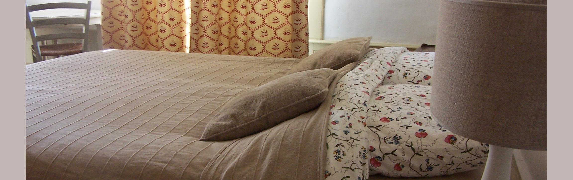opgemaakt bed met schemerlamp