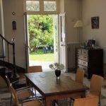 tafel in de hal met openstaande deuren naar tuin